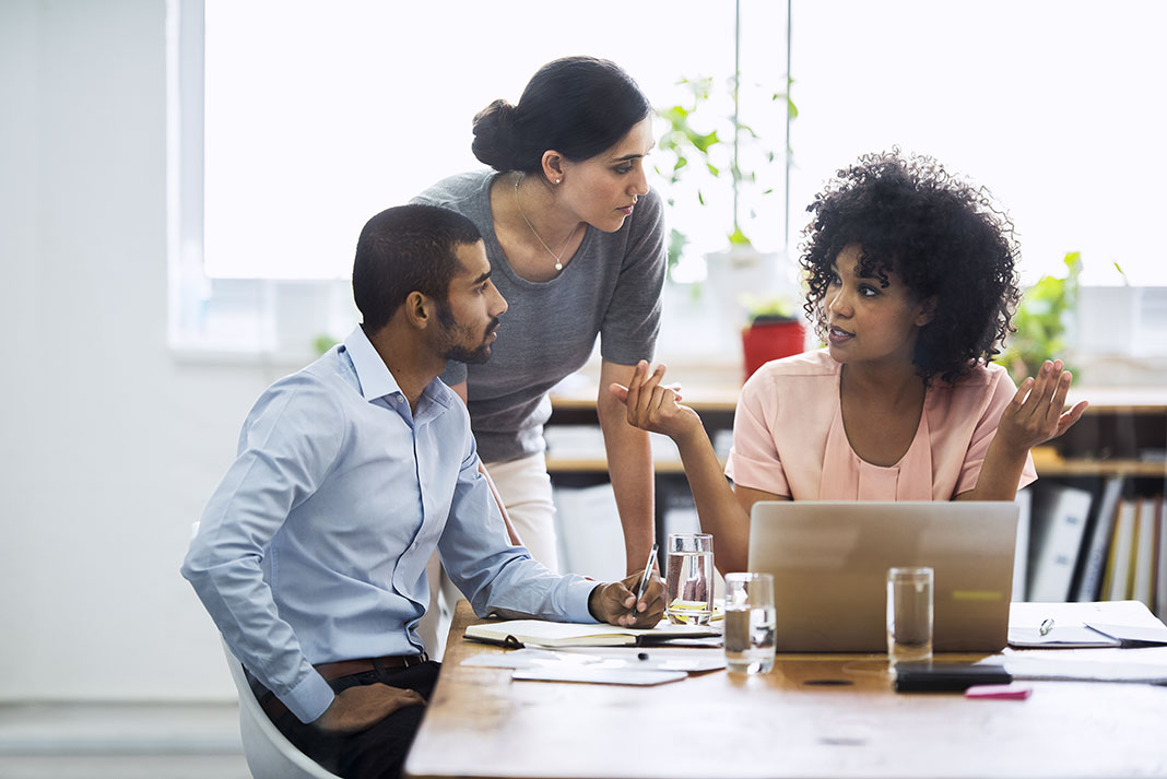 Three workers in discussion in office with laptop