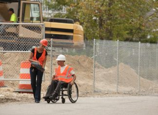 Construction woman showing clipboard to construction man in a wheelchair at a jobsite