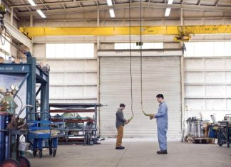 Two factory workers operating gantry cranes